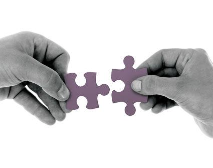 Two hands joining two puzzle pieces, small.